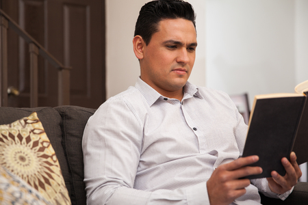 Young Latin man very concentrated on a novel he is reading at home