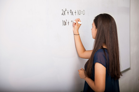 person writing: Cute teenager writing an equation in a white board at school Stock Photo