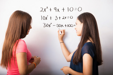 Cute young high school students solving some algebra equations on a white board photo