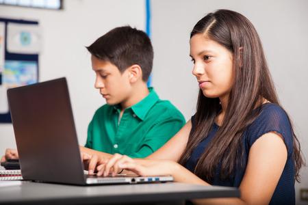 school teens: Beautiful teenage girl using a laptop computer at school