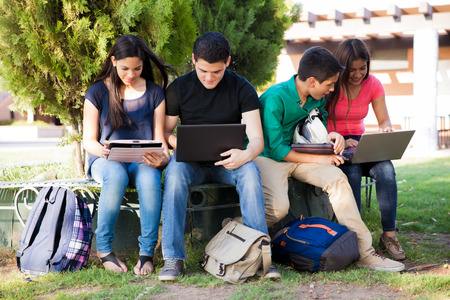 Group of teenagers social networking using several tech devices in high school photo