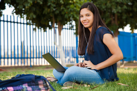 high school girl: Pretty Latin teenage girl using a laptop and wearing earbuds while doing her homework outdoors Stock Photo