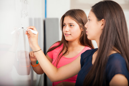algebra: Couple of female high school students writing on a white board during class