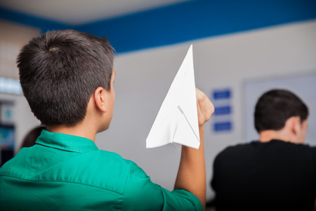 misconduct: Naughty high school student throwing a paper plane during class Stock Photo