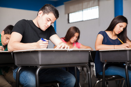 Several high school students taking a test in a classroom