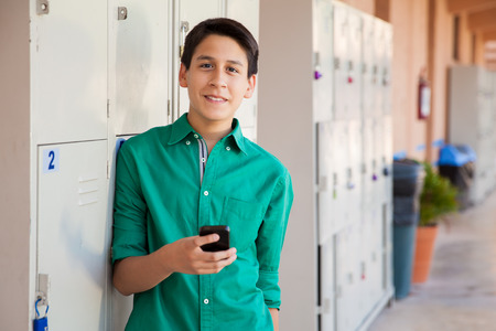 Handsome Latin boy using his cell phone in a school hallway Фото со стока - 29346781