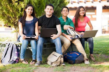 Groep van middelbare scholieren met behulp van alle soorten apparaten, terwijl opknoping uit Stockfoto