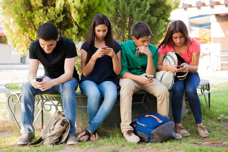 ignoring: Group of teenage boys and girls ignoring each other while using their cell phones at school