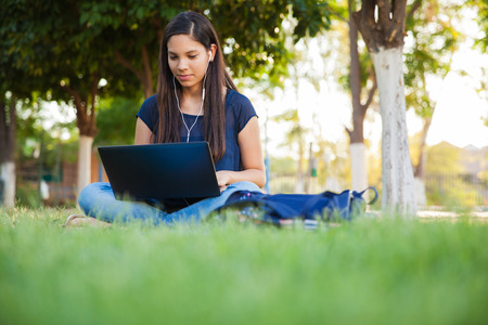 junior student: Beautiful teenage girl using a laptop and earbuds outdoors