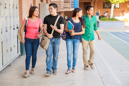 Group of high school students walking and talking in the hallway photo