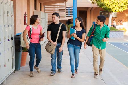 młodzież: Grupa licealistów rozmawiając i śmiejąc się w korytarzu pomiędzy klasami Zdjęcie Seryjne