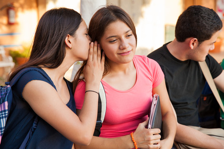 Cute female friends talking in secret about a boy they like at school photo