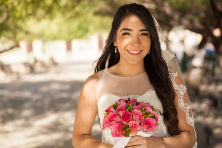 Beautiful Hispanic young bride wearing a veil and smiling outdoors photo