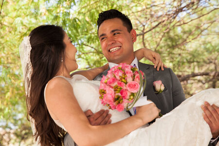 carrying: Attractive Hispanic groom carrying his bride and looking at her outdoors