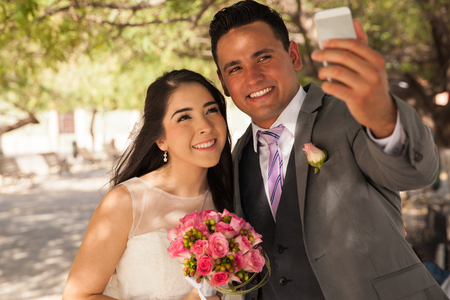 Beautiful Hispanic bride and groom taking a selfie with a mobile phone outdoors photo