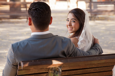 Portrait of a happy bride sitting on a bench with the groom and looking back