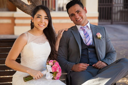 Beautiful bride and her good-looking groom sitting on a bench and smiling on their wedding day Stock Photo