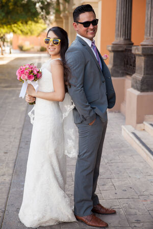 Full length portrait of a bride and groom back to back wearing sunglasses outside a church photo