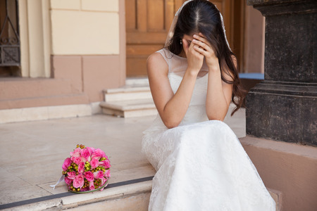 beautiful bride: Hopeless bride crying outside a church after being stood up on her wedding day