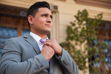 Handsome Hispanic man in a suit fixing his tie outdoors photo