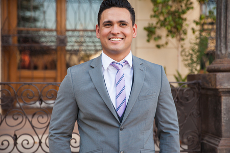 wedding portrait: Portrait of a handsome Hispanic groom on his wedding day outside a church