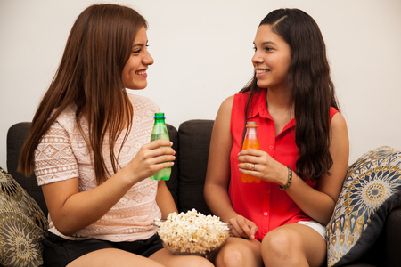 cute couple of teenage girlfriends drinking soda and eating popcorn before watching a movie photo - Cute Pictures Of Teens