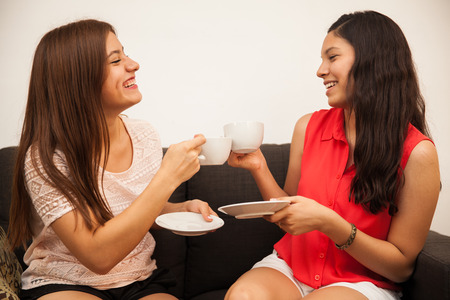 Pretty Hispanic teenagers having fun and making a toast with coffee cups at home photo
