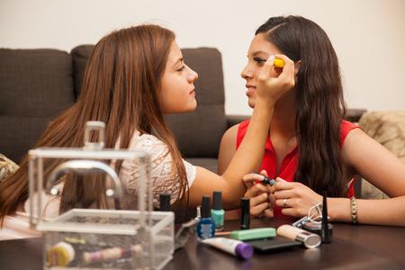 adolescencia: Adolescentes hispanos que se preparan para salir juntos y poner un poco de maquillaje en