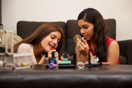 Beautiful teens getting ready and putting on some makeup at home Stock Photo