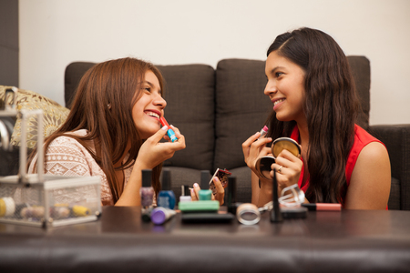 puberty: Pretty teenage friends putting some makeup on while hanging out at home