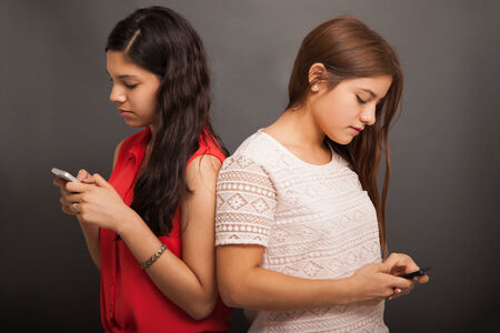 sms: Hispanic teens using their own smart phone and ignoring each other