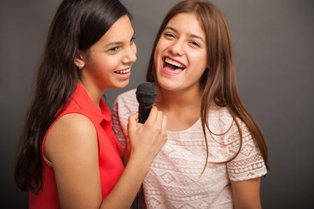 cute teen girl: Веселые подростки поют песню с микрофоном и весело