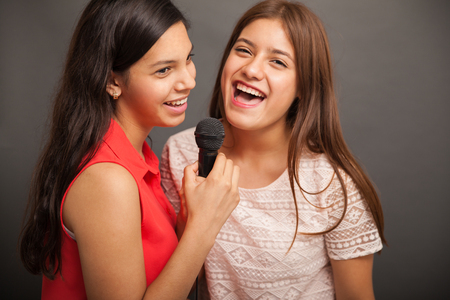 Cheerful teenagers singing a song with a microphone and having fun photo