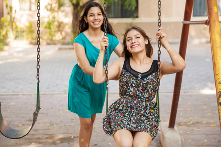 Latin teenage friends playing in a swing and having fun photo