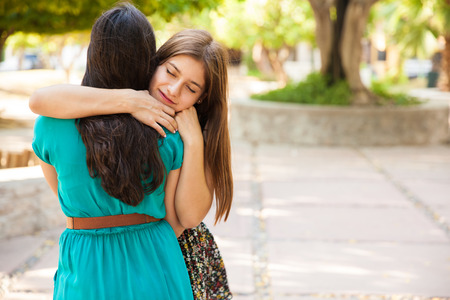 Beautiful teenage friends hugging each other with their eyes closed  Lots of copy space Stock fotó