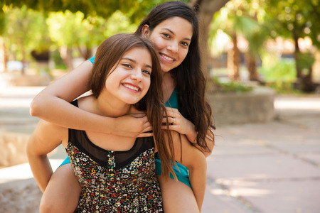 puberty: Having some fun piggyback riding my best friend while hanging out at a park Stock Photo