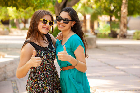 best friends: Cute teenage best friends with their thumbs up and sunglasses
