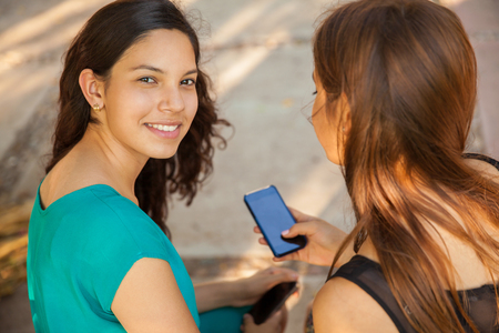 Beautiful Hispanic teens social networking and texting with their cell phones Stock Photo