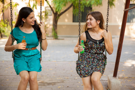 Beautiful teenage friends hanging out at a park and drinking soda photo