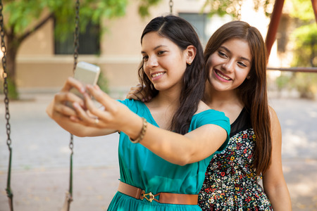Hispanic teenage best friends taking a selfie with a smart phone photo