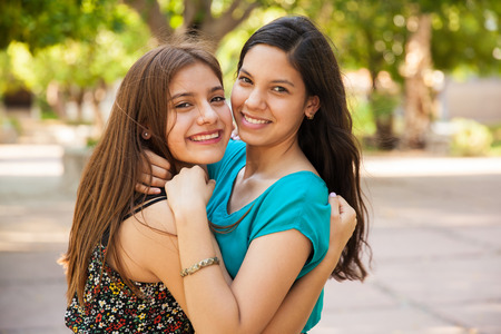 Beautiful Hispanic teens hugging each other and smiling at a park
