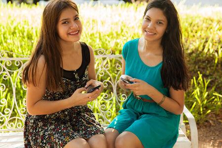 adolescencia: Adolescentes hispanos hermosa Texting junto con su propio teléfono celular y sonriendo