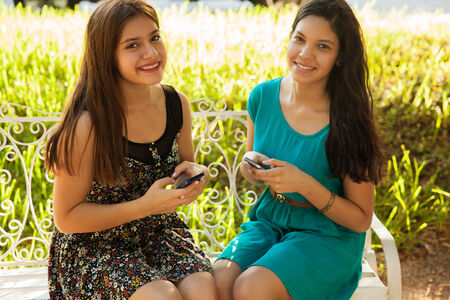 Beautiful Hispanic teens texting together with their own cell phone and smiling
