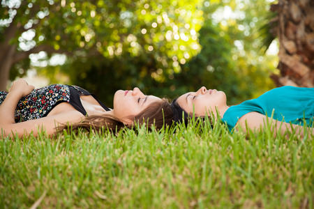 puberty: Beautiful teenage friends napping and relaxing together at a park