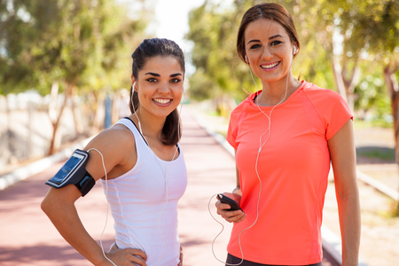 woman on cell phone: Beautiful girls wearing armbands and earbuds and ready to go for a run together Stock Photo