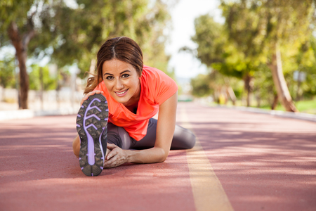 touching toes: Young Hispanic woman touching her toes for stretching at a running track Stock Photo