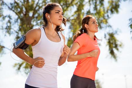 pista de atletismo: Dos corredoras trabajando mientras se escucha m�sica en su tel�fono m�vil en un brazalete Foto de archivo