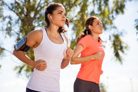 jogging track: Two female runners working out while listening to music on their mobile phone on an armband