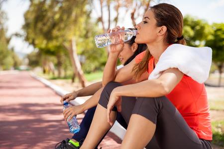 Jeune brunette hispanique et son amie l'eau potable à partir d'une bouteille après leur séance d'entraînement Banque d'images - 31230590
