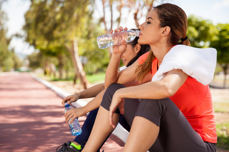 Young Hispanic brunette and her friend drinking water from a bottle after their workout Stock Photo